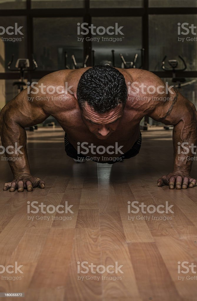 male bodybuilder doing push ups at the floor royalty-free stock photo