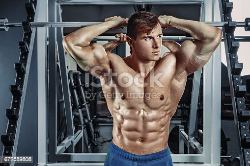 istock Male bodybuilder, fitness model trains in the gym 672589808