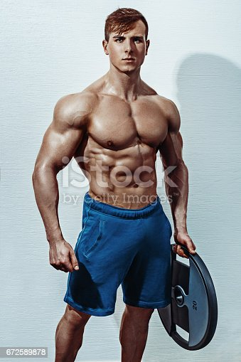 istock Male bodybuilder, fitness model trains in the gym 672589878