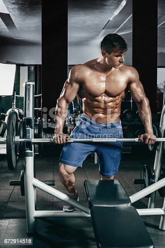 istock Male bodybuilder, fitness model trains in the gym 672914518