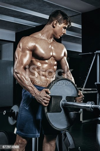 istock Male bodybuilder, fitness model trains in the gym 672914568