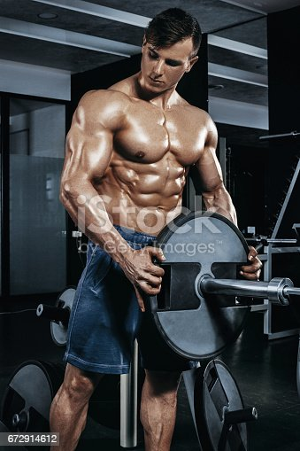 istock Male bodybuilder, fitness model trains in the gym 672914612