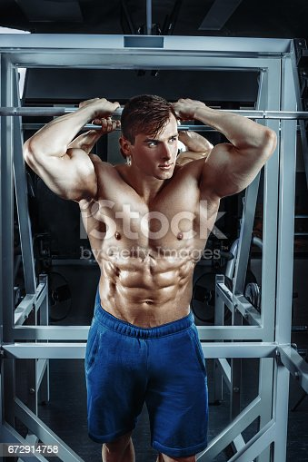 istock Male bodybuilder, fitness model trains in the gym 672914758