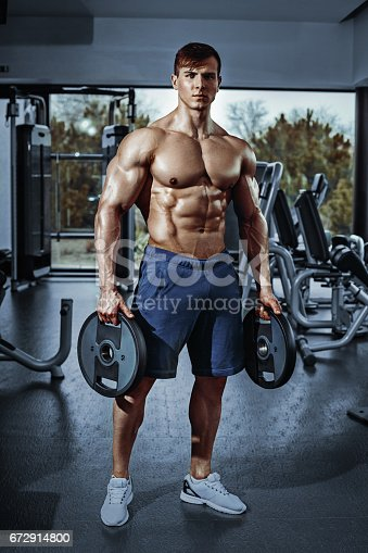 istock Male bodybuilder, fitness model trains in the gym 672914800