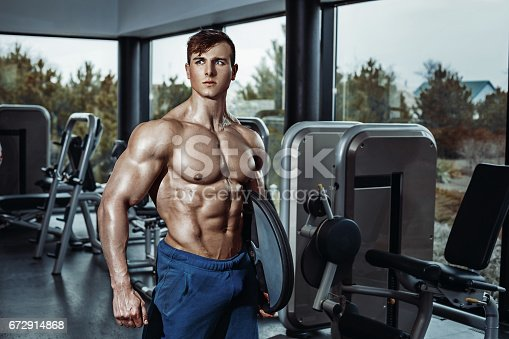 istock Male bodybuilder, fitness model trains in the gym 672914868