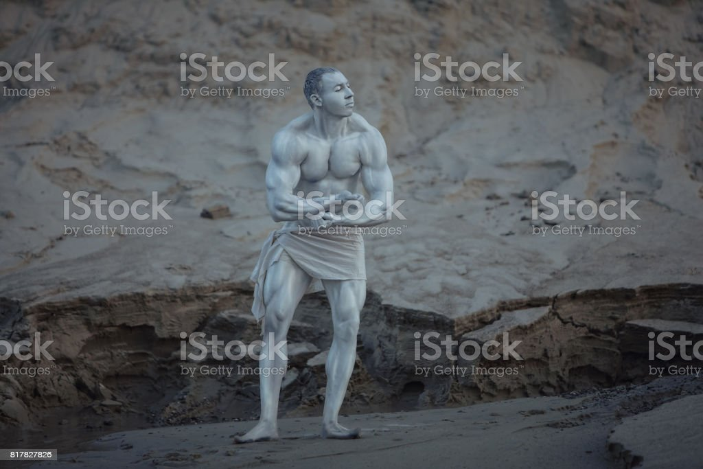 Male bodybuilder poses as a statue. stock photo