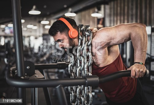 Side view of male strong bodybuilder training with weight steel chain, listening music with wireless headphones