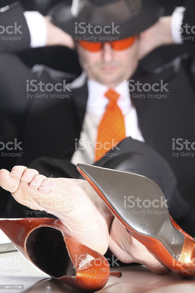 Male boss lying his orange high heels on desk royalty-free stock photo