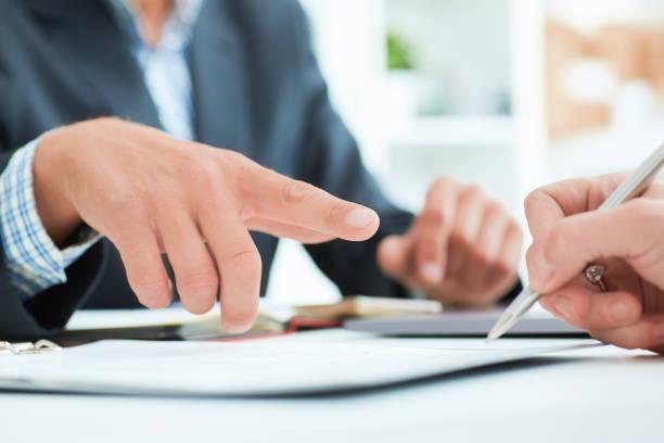 männlichen vorgesetzten empfiehlt, dass seine mitarbeiter einen vertrag im büro. business-mann weist auf den ort, wo es notwendig, die signatur zu setzen - rechtsassistent stock-fotos und bilder