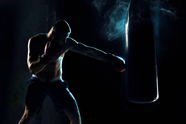 Cтоковое фото Male boxer boxing in punching bag