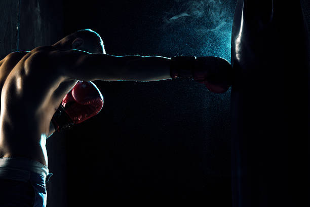 Male boxer boxing in punching bag stock photo