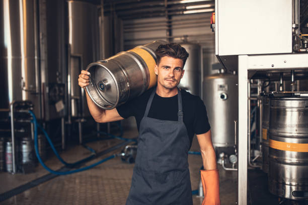 Male brewer carrying metal container at brewery factory stock photo