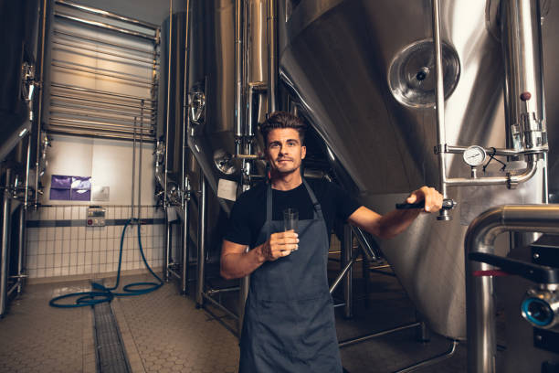 Male brewer standing by tank in brewery stock photo
