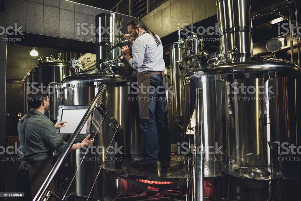 Male brewery workers in aprons stock photo