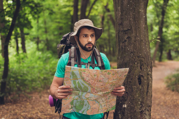 male brunet bearded confused tourist got lost in the forest, holding map, looking far, trying to find the way. he has a backpack, all needed for overnight stay. search the trail way - wilderness stock pictures, royalty-free photos & images