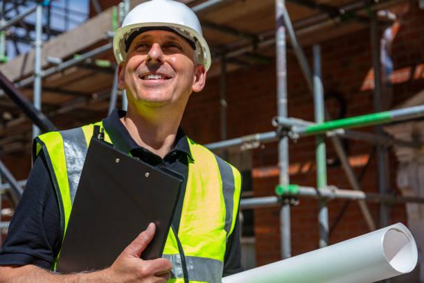 Capataz constructor masculino, obrero, contratista o arquitecto en el sitio de construcción sosteniendo portapapeles negro y planos arquitectónicos - foto de stock
