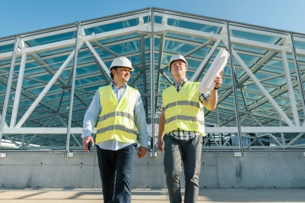 Hombres constructores avanzar en techo de obra. Concepto de construcción, desarrollo, trabajo en equipo y personas - foto de stock