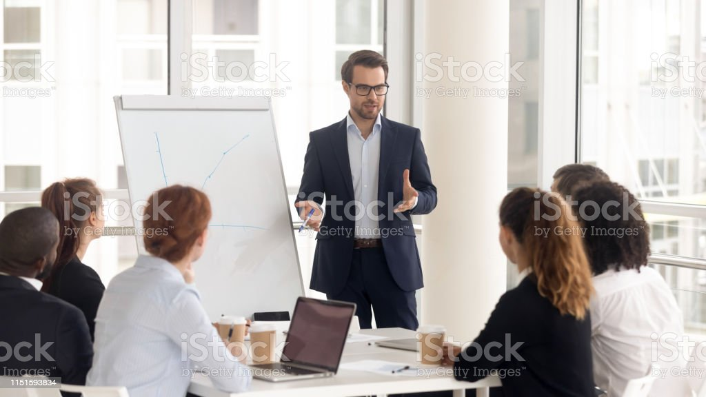 Male business coach speaker in suit give flipchart presentation Male business coach speaker in suit give flipchart presentation, speaker presenter consulting training persuading employees client group, mentor leader explain graph strategy at team meeting workshop Business Stock Photo