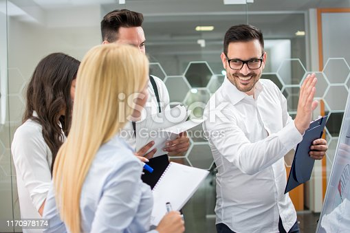 istock Male business coach speaker in white shirt give flipchart presentation to his colleagues. 1170978174