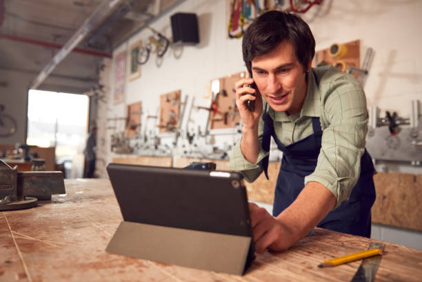 Male Business Owner In Workshop Using Digital Tablet And Making Call On Mobile Phone stock photo