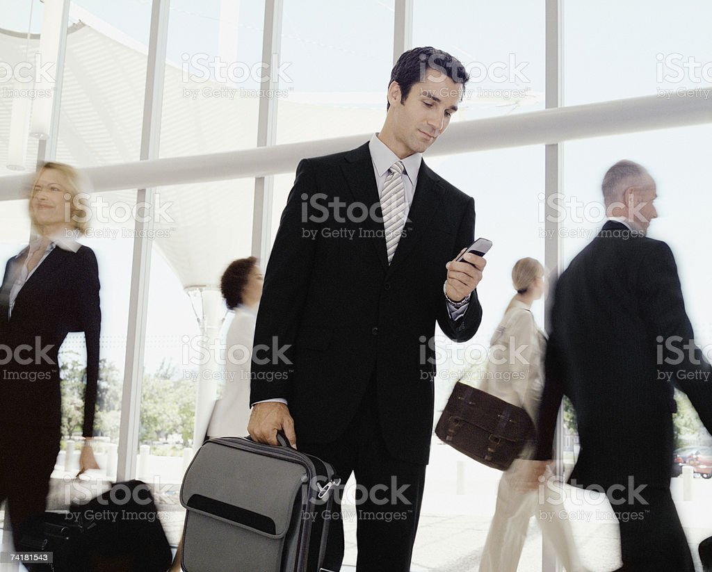 Male business traveler with cell phone stock photo