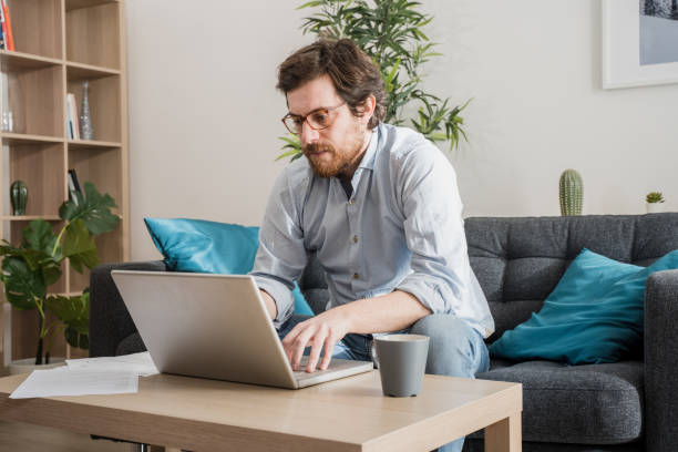Male businessman working on laptop from home stock photo