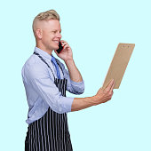 istock Male butcher standing in front of blue background wearing apron and holding contract and using mobile phone 1246342272