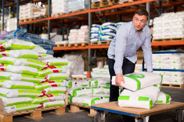 Male buyer storing fertilizer bags on trolley in hardware store stock photo