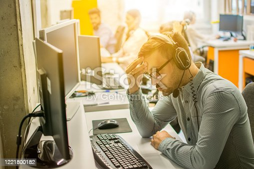 658516626 istock photo Male Call center operator wearing headset suffering from headache at office 1221800182