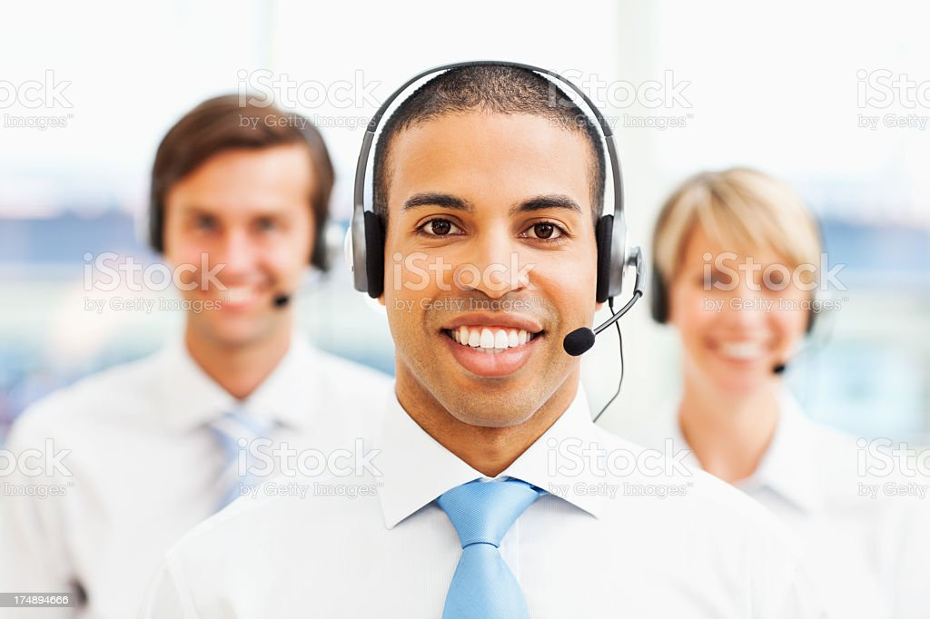 Male Call Centre Representative With Coworkers In Background royalty-free stock photo