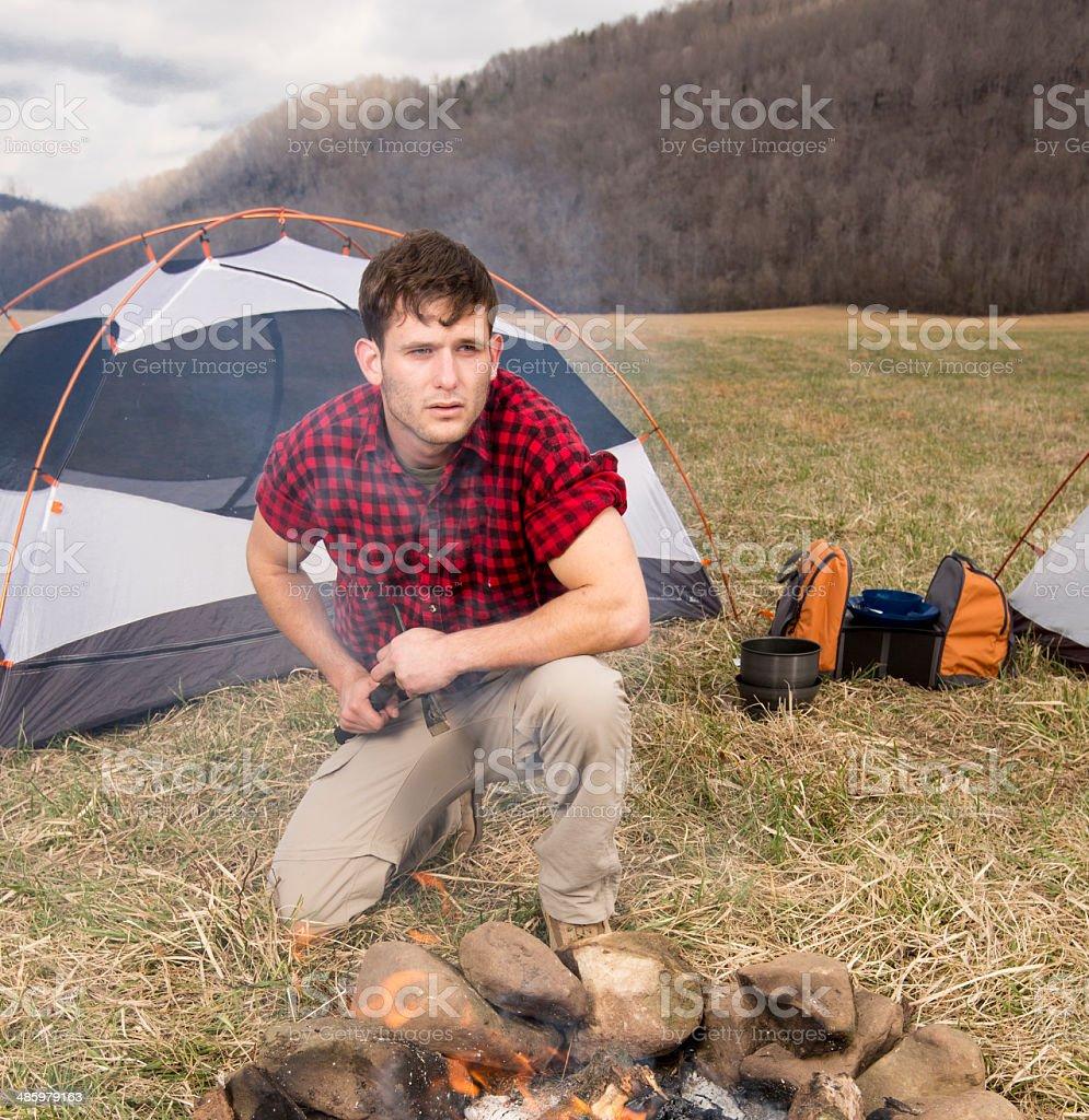 Male Camper Getting the Fire Started stock photo