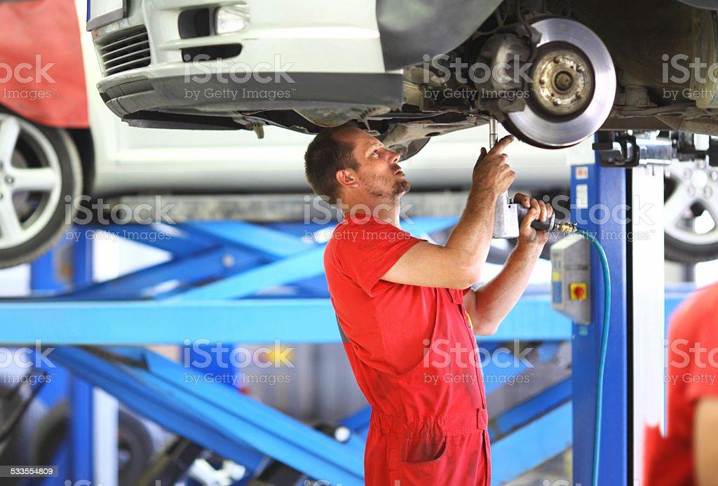 Male car mechanic repairing break system on vehicle. stock photo