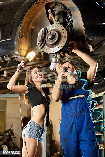 962888586 istock photo Male car mechanic repairing the car with pneumatic key on hydraulic lift and girl in a frank dressed is standing next to him holding a flashlight. 899675300