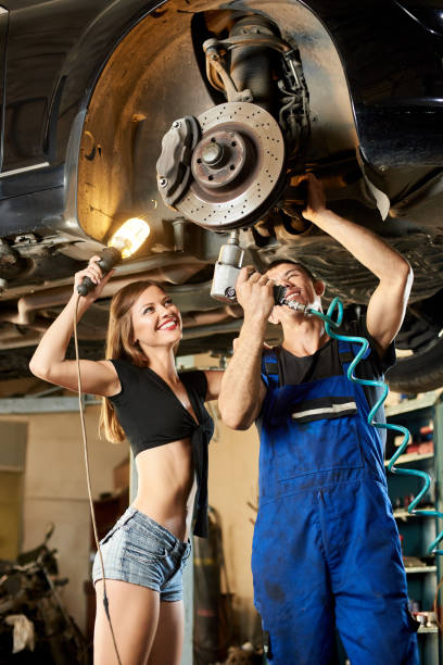 Male car mechanic repairing the car with pneumatic key on hydraulic lift and girl in a frank dressed is standing next to him holding a flashlight. stock photo
