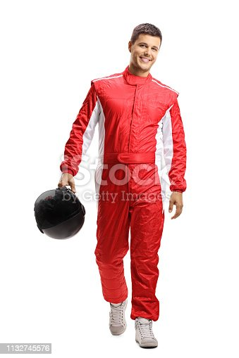 Full length portrait of a male car racer holding a helmet and walking towards the camera isolated on white background