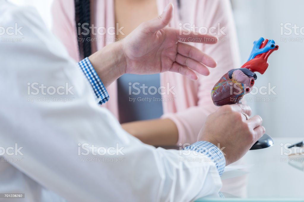 Male cardiologist discusses diagnosis with patient stock photo