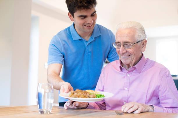 männlicher Pflegeassistent Serving Meal To Senior Male Sitzen am Tisch – Foto