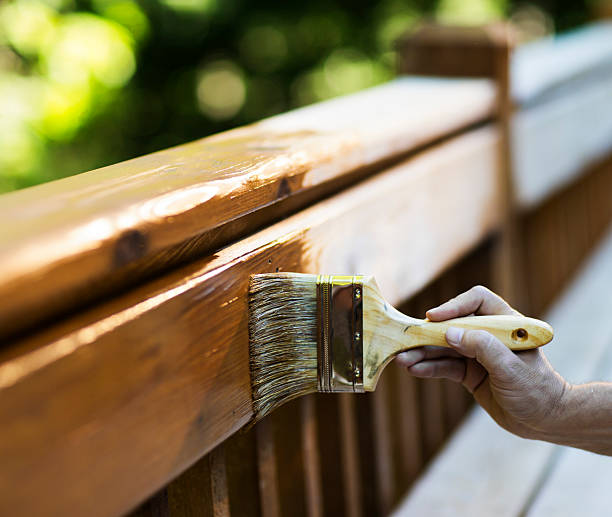 Male Carpenter Applying Varnish To Wooden Furniture. stock photo