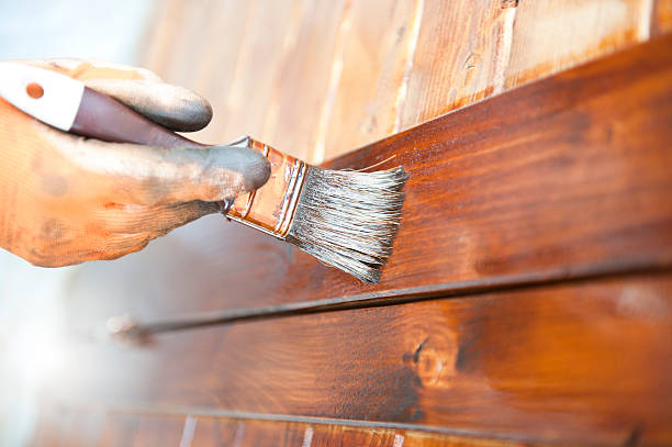 male carpenter applying varnish to wooden furniture - houtbeits stockfoto's en -beelden