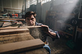 Young man working in a carpentry workshop and blowing sawdust off a piece of wood.