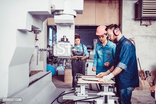 Male Carpenter Explaining How Machine Works To a New Female Employ