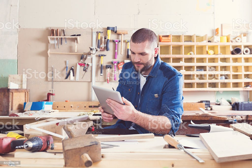 Male carpenter in a construction workshop, using a digital tablet stock photo