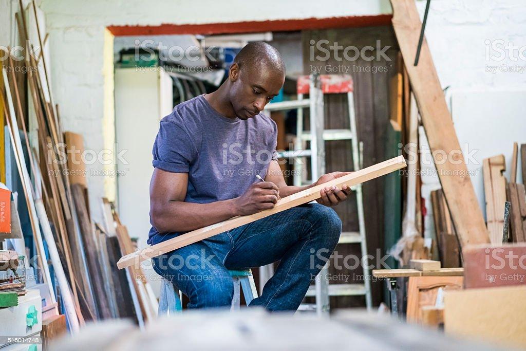 Male carpenter marking on plank in workshop stock photo