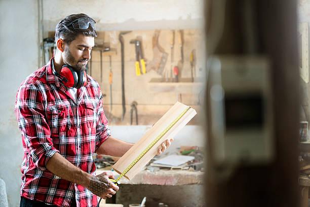 male carpenter measuring the board - waldhandwerk stock-fotos und bilder
