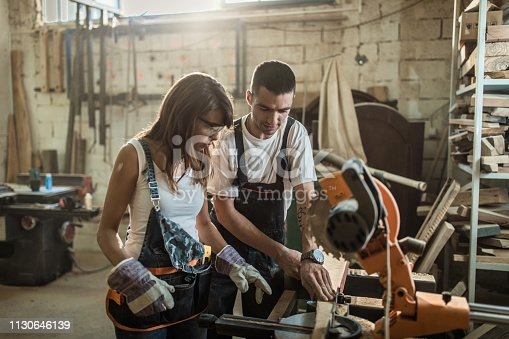 Female and male carpenters using electric saw while working on piece of wood in a workshop. Focus is on man.
