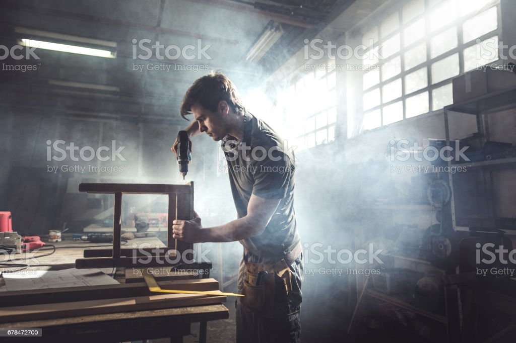 Male carpenter using drill to repair a chair in a workshop.