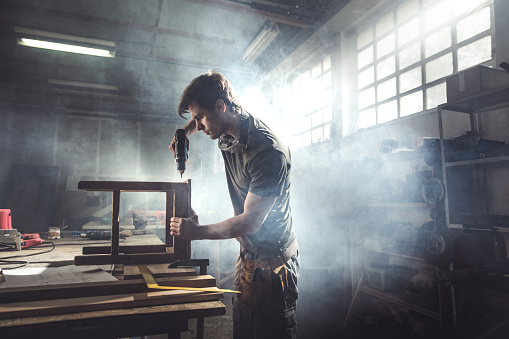 530997702 istock photo Male carpenter using drill to repair a chair in a workshop. 678472700