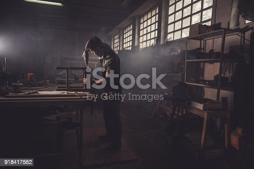 530997702istockphoto Male carpenter using drill to repair a chair in a workshop. 918417552