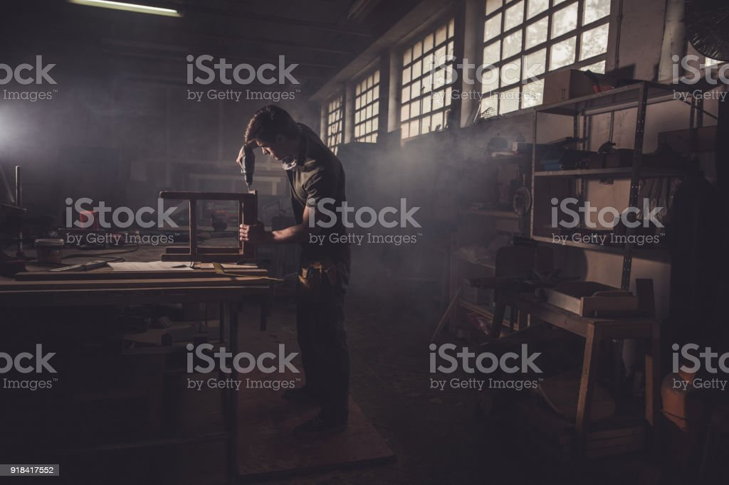 Male carpenter using drill to repair a chair in a workshop. stock photo