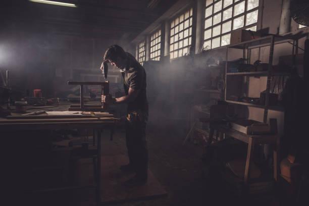 manliga snickare med borr för att reparera en stol i en workshop. - hantverkare bildbanksfoton och bilder